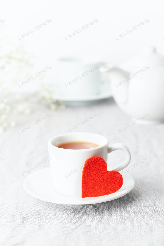 Valentine's Day. Morning breakfast for two with tea and flowers. Red felt heart is symbol of lovers