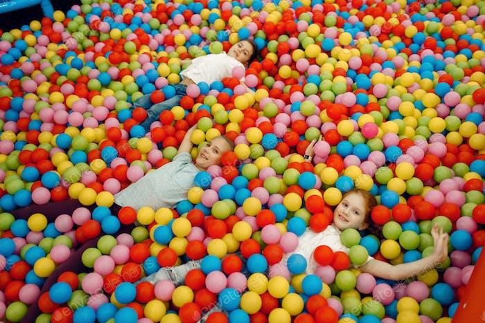 Kinder liegen unter vielen Bällen, Spielplatz