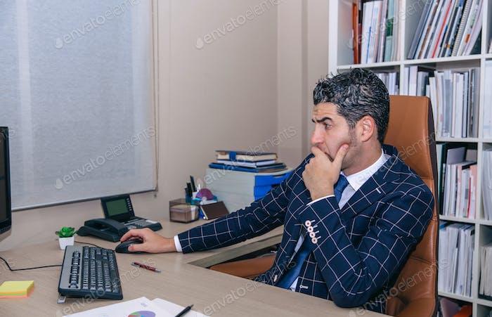 Бизнесмен, работающий с компьютером в офисе