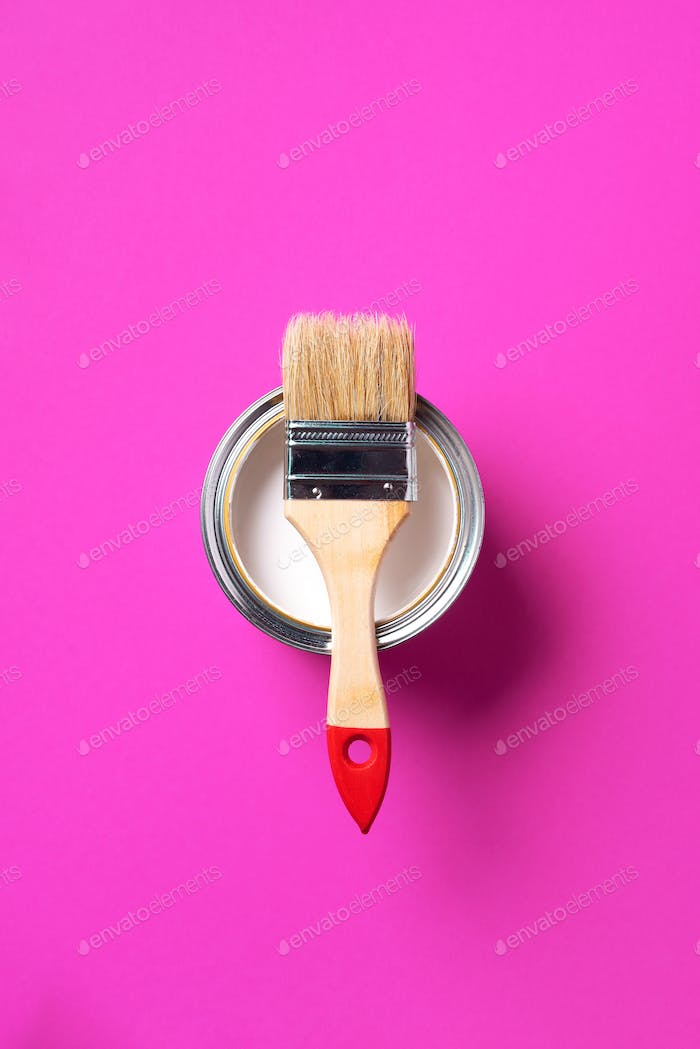 Brush and open paint can with on trendy yellow background. Top view, copy space. Appartment