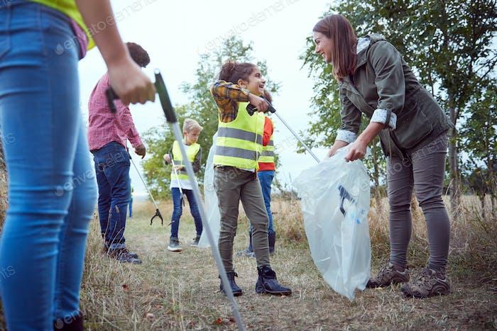 Erwachsene Teamleiter mit Gruppe von Kindern im Outdoor-Aktivitätslager Sammeln von Wurf zusammen