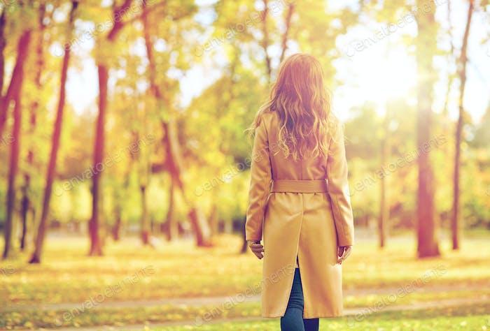 schöne junge Frau zu Fuß im Herbst Park