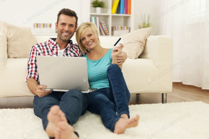 Happy loving couple sitting on the floor and using laptop and showing credit card
