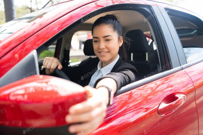 Woman moving rear view wing mirror in car.
