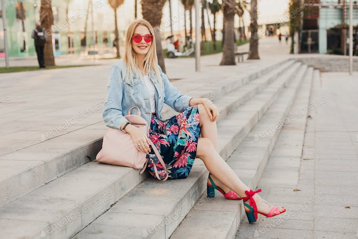 pretty smiling woman sitting in city street