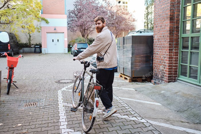 Young attractive casual man walking through street with classic bicycle