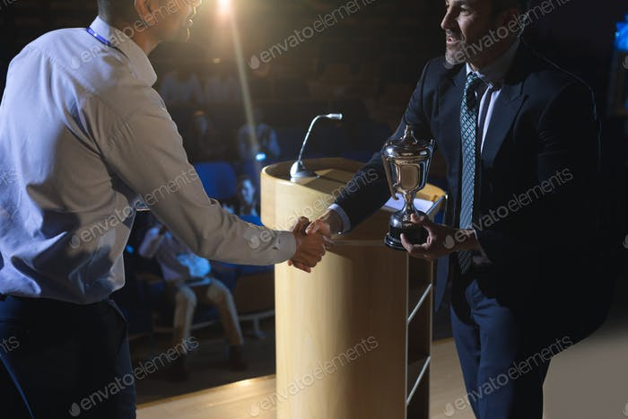 Businessman appreciating mixed race business male executive on stage in auditorium