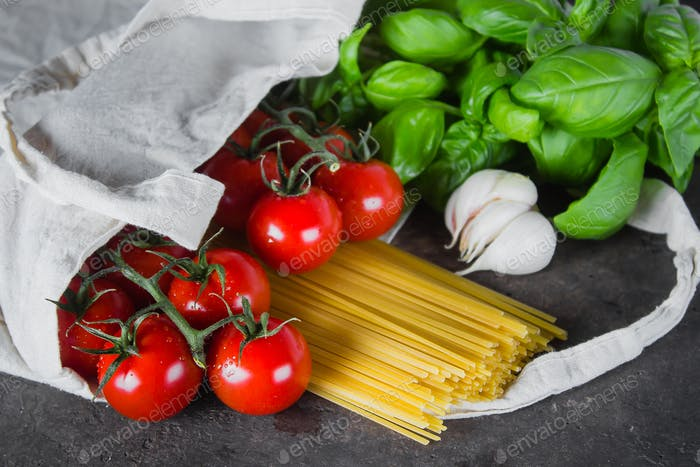 Basil, tomatoes cherry, garlic in fabric bag on dark table background. Reusable bag with groceries.