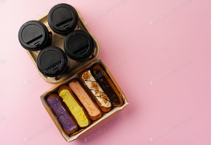 Box of eclairs with takeaway coffee cups on pink background