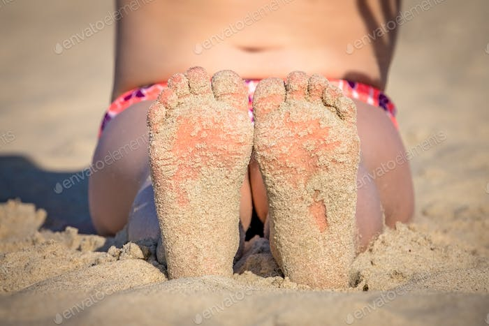Little girls feet in the beach sand