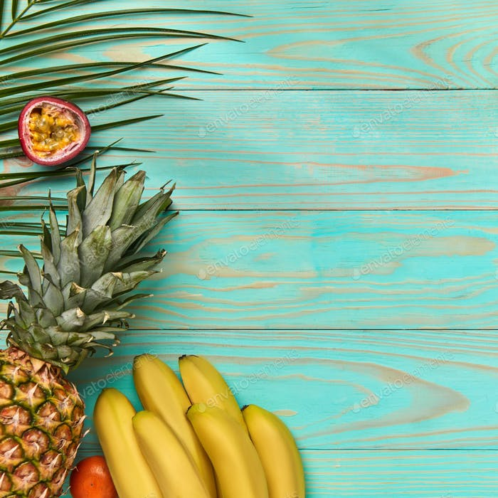 Whole pieces of juicy exotic fruits and green palm leaves on a blue wooden background with space for
