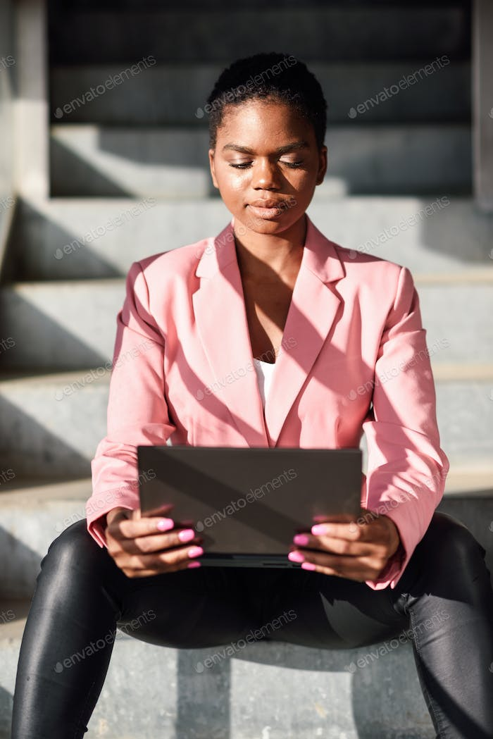 Black businesswoman sitting on urban steps working with a laptop computer