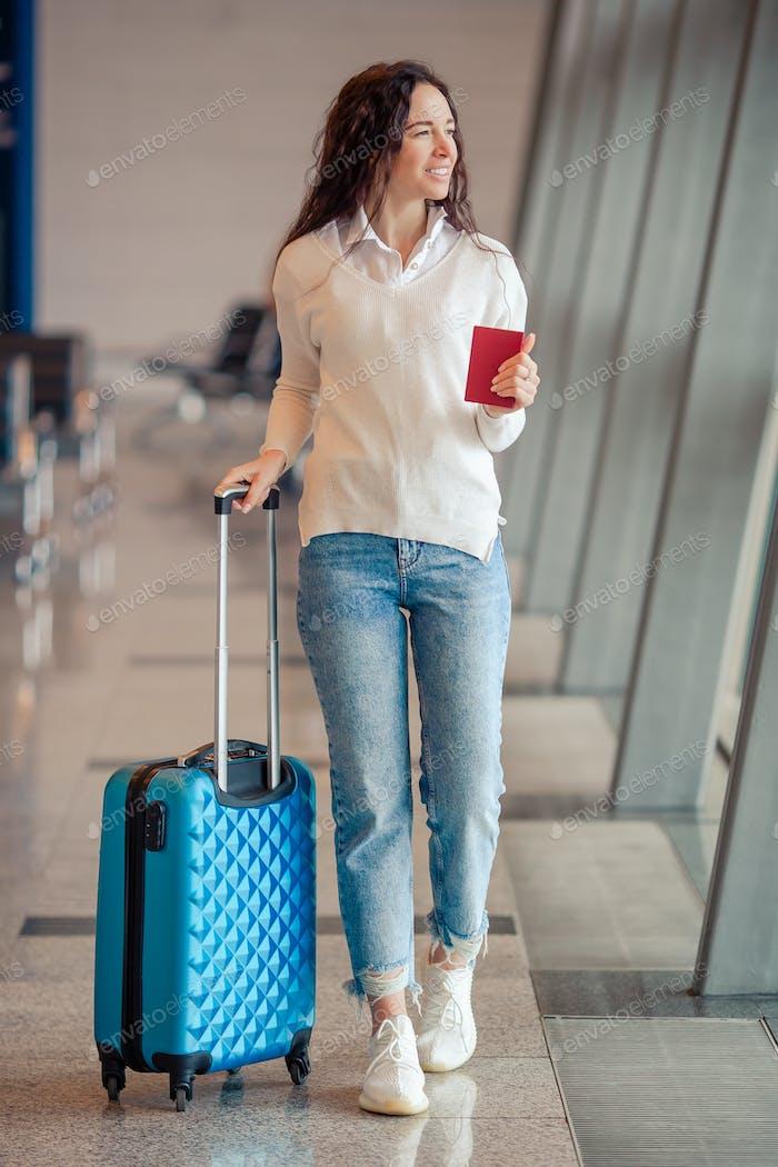 Junge Frau mit Gepäck im internationalen Flughafen. Fluggast in einer Flughafenlounge wartet
