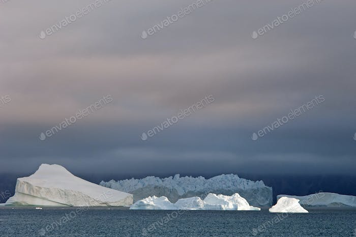 Sunset sky, with heavy cloud and floating icebergs with smooth eroded shapes on the waters of Baffin