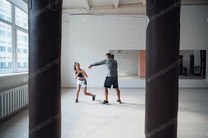 Ein attraktiver junger Boxer lehrt seine Freundin Boxtechniken in einem Loft für Boxen ausgestattet