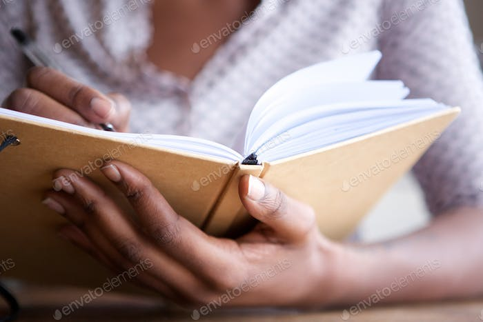 Close up female hands holding pen and book