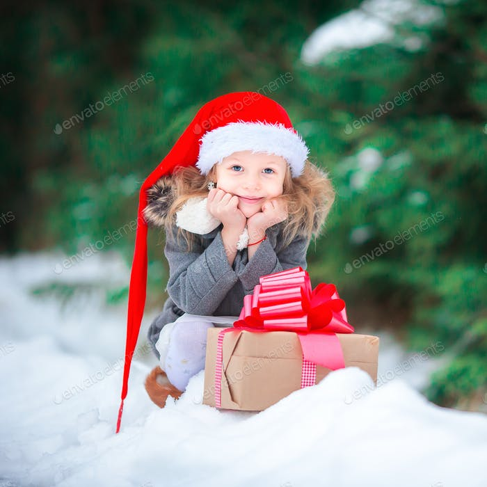 Adorable happy girl with christmas box gift in winter outdoors on Xmas eve
