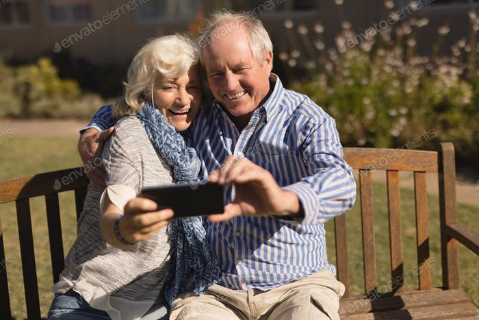 Front view of active senior Caucasian couple taking selfie with mobile phone in the park