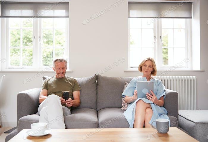 Anti-Sozial Seniorenpaar sitzen auf Sofa zu Hause mit digitalem Tablet Und Handy