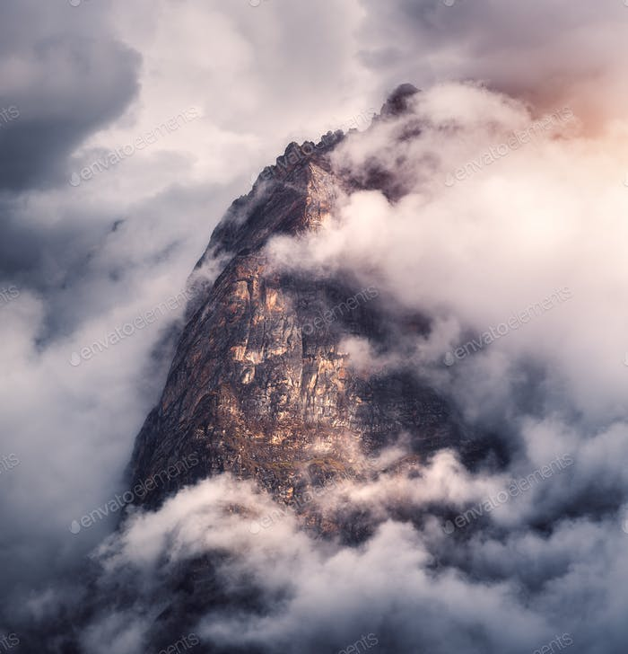 Majestical mountains in clouds in overcast evening