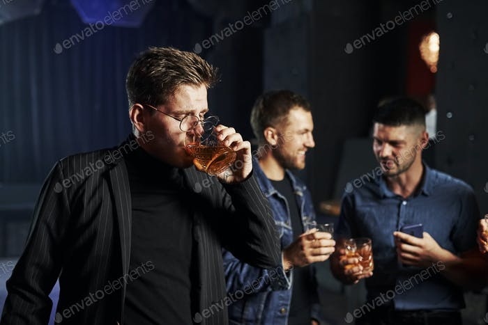 People have fun in the night club. With alcohol in hands