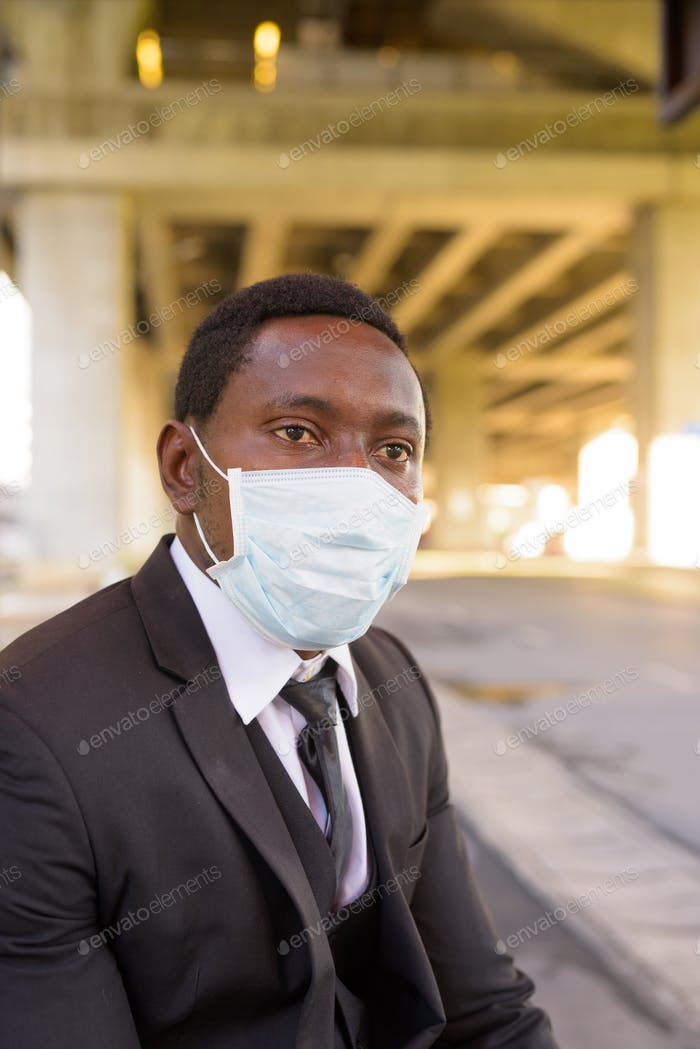 African businessman with mask thinking and waiting at the bus stop