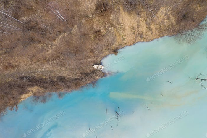 Aerial drone view of a boat in a turquoise lake contaminated with cyanide mining residuals