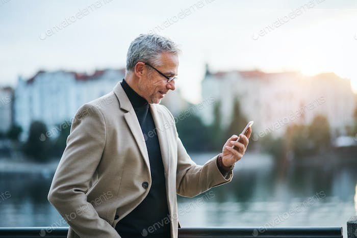 Mature businessman with smartphone standing by river in Prague city, taking selfie.