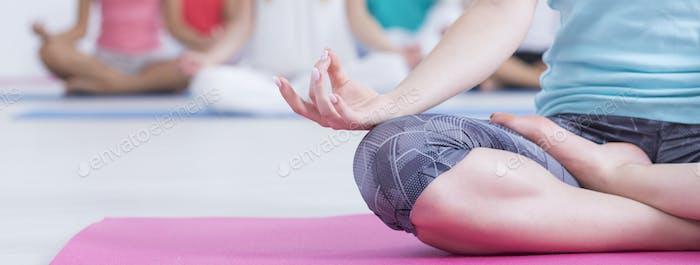 Woman meditating while doing lotus flower
