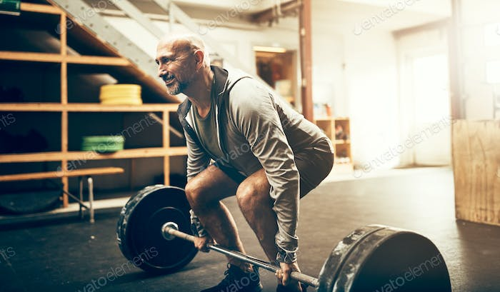 Fit mature man lifting heavy weights during a workout session