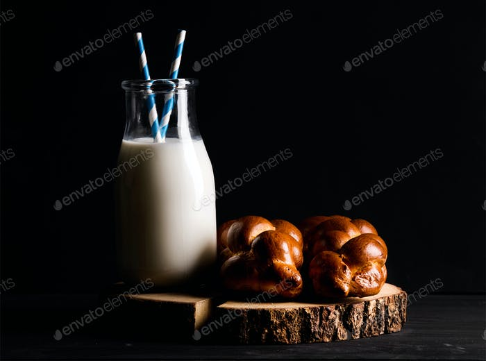 Bottle of milk and loaf buns on rustic wooden board over dark background