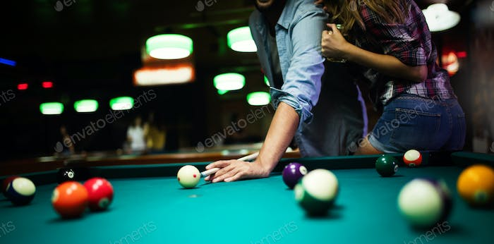 Couple dating, flirting and playing billiard in a pub