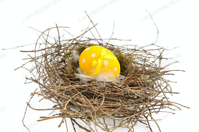A yellow easter egg in nest on a white background