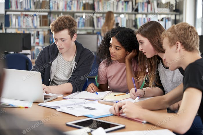 Group Of College Students Collaborating On Project In Library