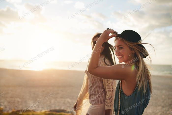 Beautiful friends enjoying a walk on the beach