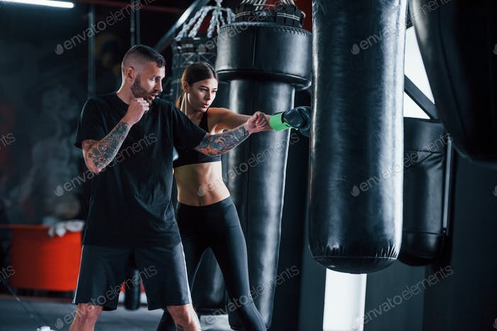 Young tattooed boxing coach teaches young woman in the gym