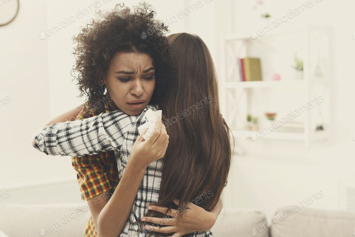 Woman hugging her depressed friend at home