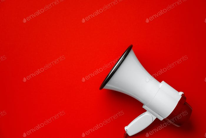 Electronic megaphone close up on red background