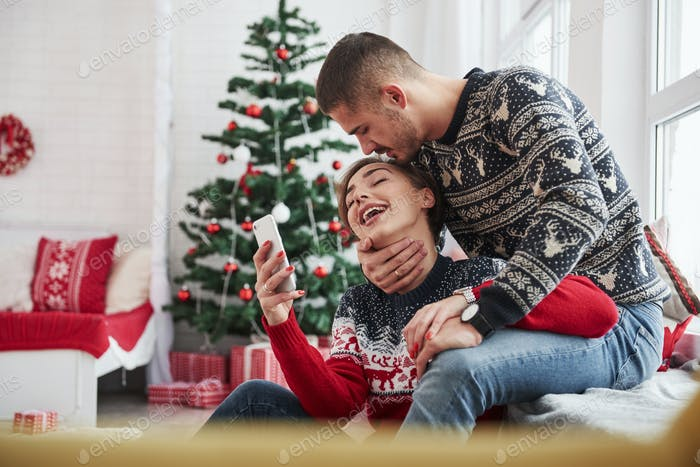 Happy young people sits on the windowsill in the room with christmas decorations