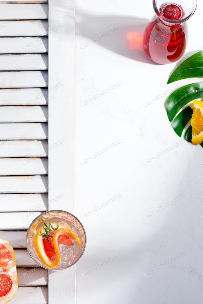 Thumbnail for Cold summer drink in a glass with slice of grapefruit and ice cubes on a white background with part