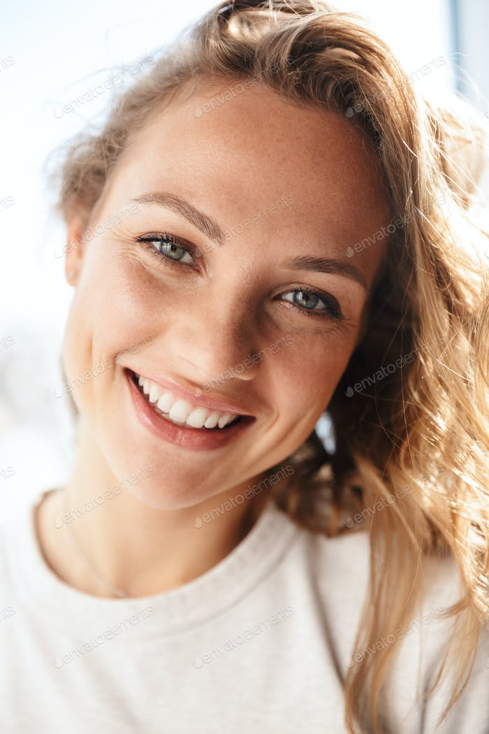 Close up of a smiling young woman standing at the window