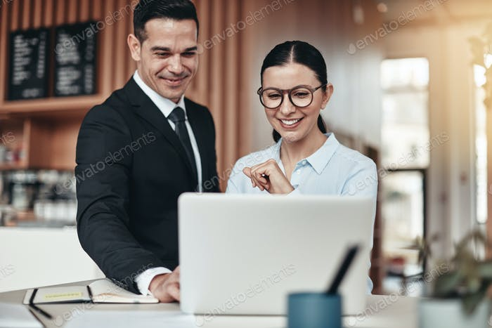 Smiling businesspeople working together at a table in an office