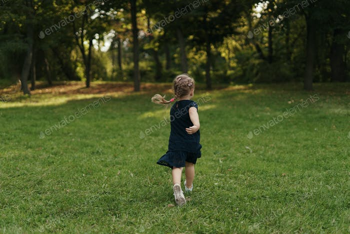 Joyful little girl running on green grass