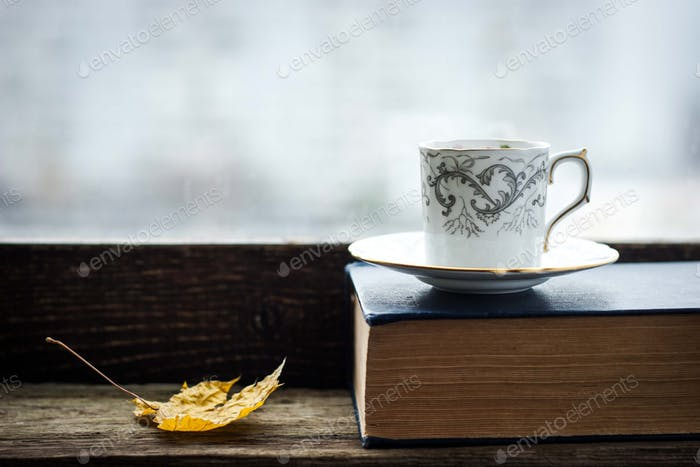 Coffee cup  with maple leaf  and old book