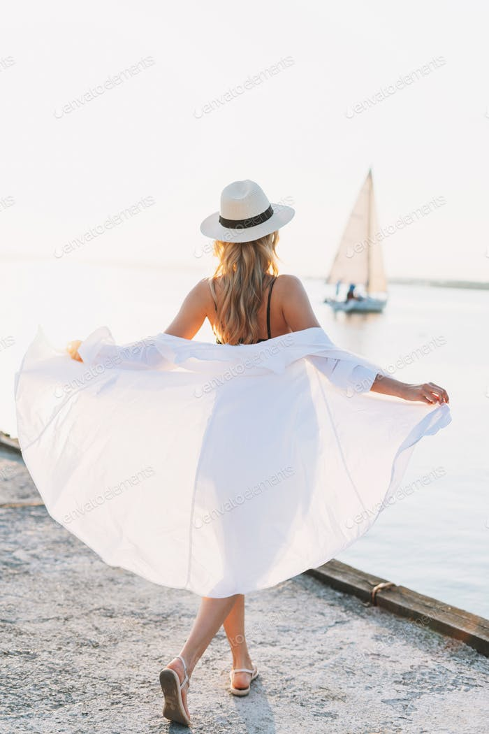 Beautiful blonde young woman in white shirt on the pier on background of sailboat on sunset