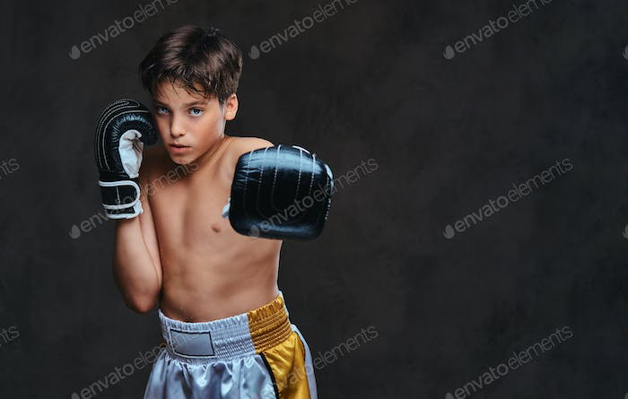 Young boxer workout in a dark studio