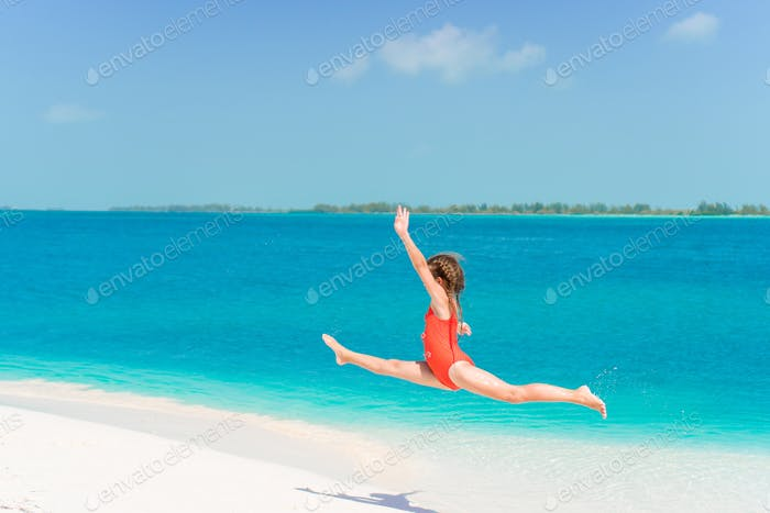 Amazing little girl at beach having a lot of fun on summer vacation