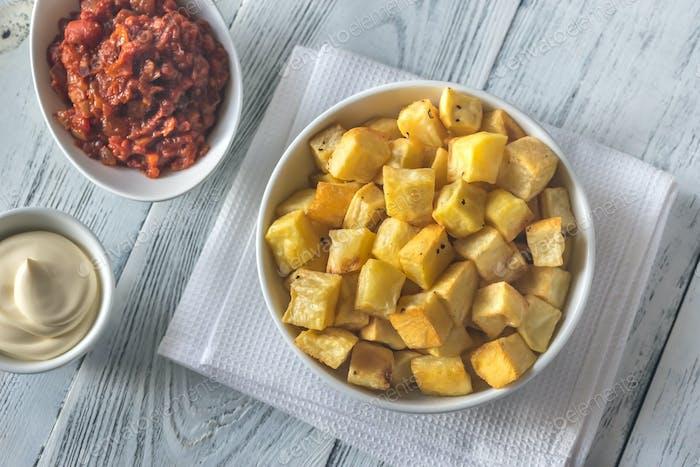 Portion of patatas bravas with sauces