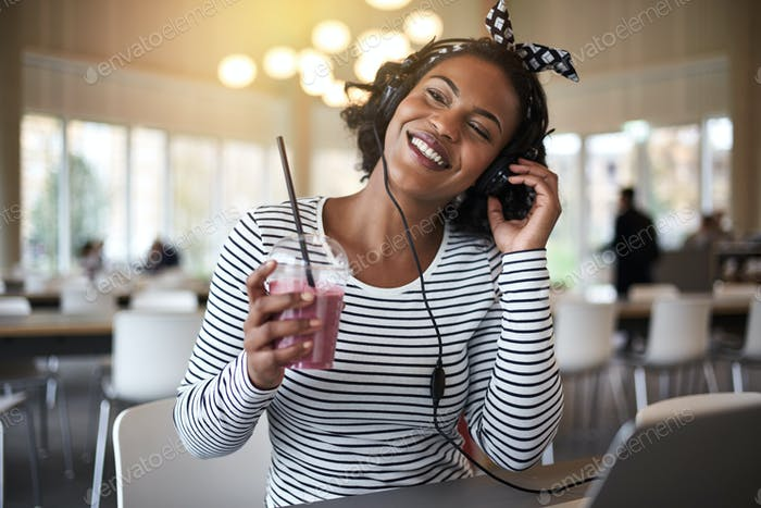 Smiling college student drinking a smoothie while listening to music