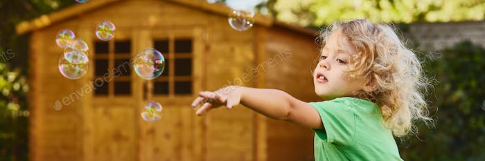 Boy with curly hair playing with bubbles